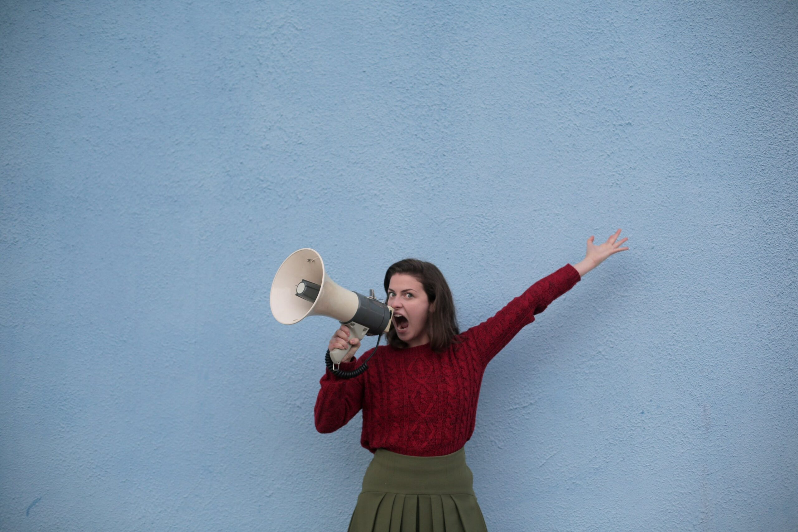 Woman shouting into her megaphone, looking at the camera in front of a muddy-blue wall, her left hand raised above her head. She's wearing a green skirt and a red jumper and she has a very intense look on her face, with her brown hair cut at her shoulders. This image was repurposed to represent using the correct voice and tone.